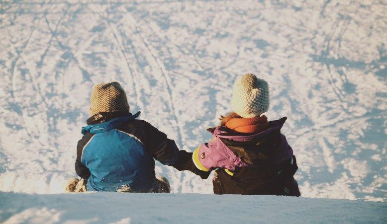 sledding holding hands